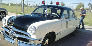 Retired Phoenix Lieutenant Mike Nikolin and the Phoenix Police Museum's 1950 Ford police car