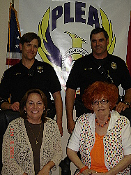 "Pictured above: Officers Paul Dobson and Rusty Stuart of the Squaw Peak Precinct, Mrs. Ann Malone of the Indian School Citywide Association and Mrs. Donna Neil of 'NAILEM""."